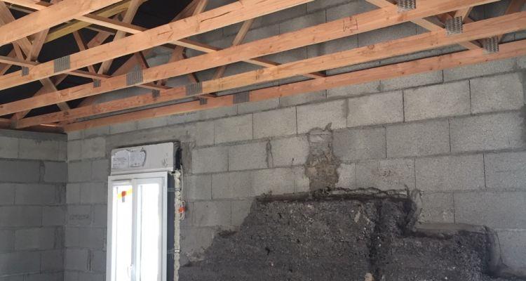Nouvelle charpente en fermettes, fenêtre et sol posés, le mur de pignon pré-existant est encore visible.